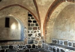 Zachodnia i północna ściana z pozostałościami średniowiecznego kościoła z kamienia
